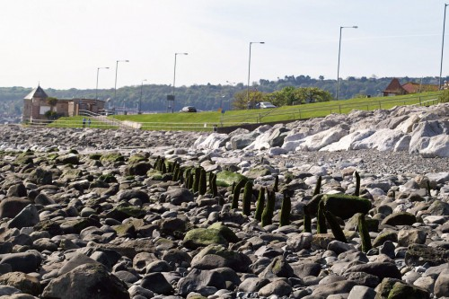 Rhos on Sea promenade from seashore with line of old fishing weir posts