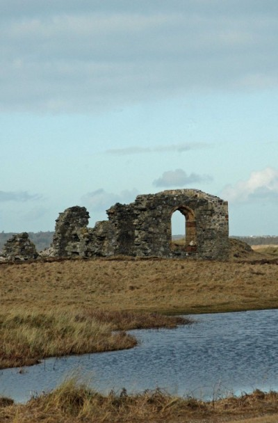 St Dwynwen's chapel across a pool of standing water