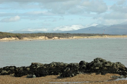 Newborough sands-people walking, kite-surfing & snowy mountains