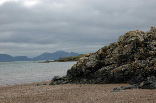 Limestone rocks on Newborough beach, tip of Llanddwyn Island behind and mountains of the Llyn Peninsular form the background